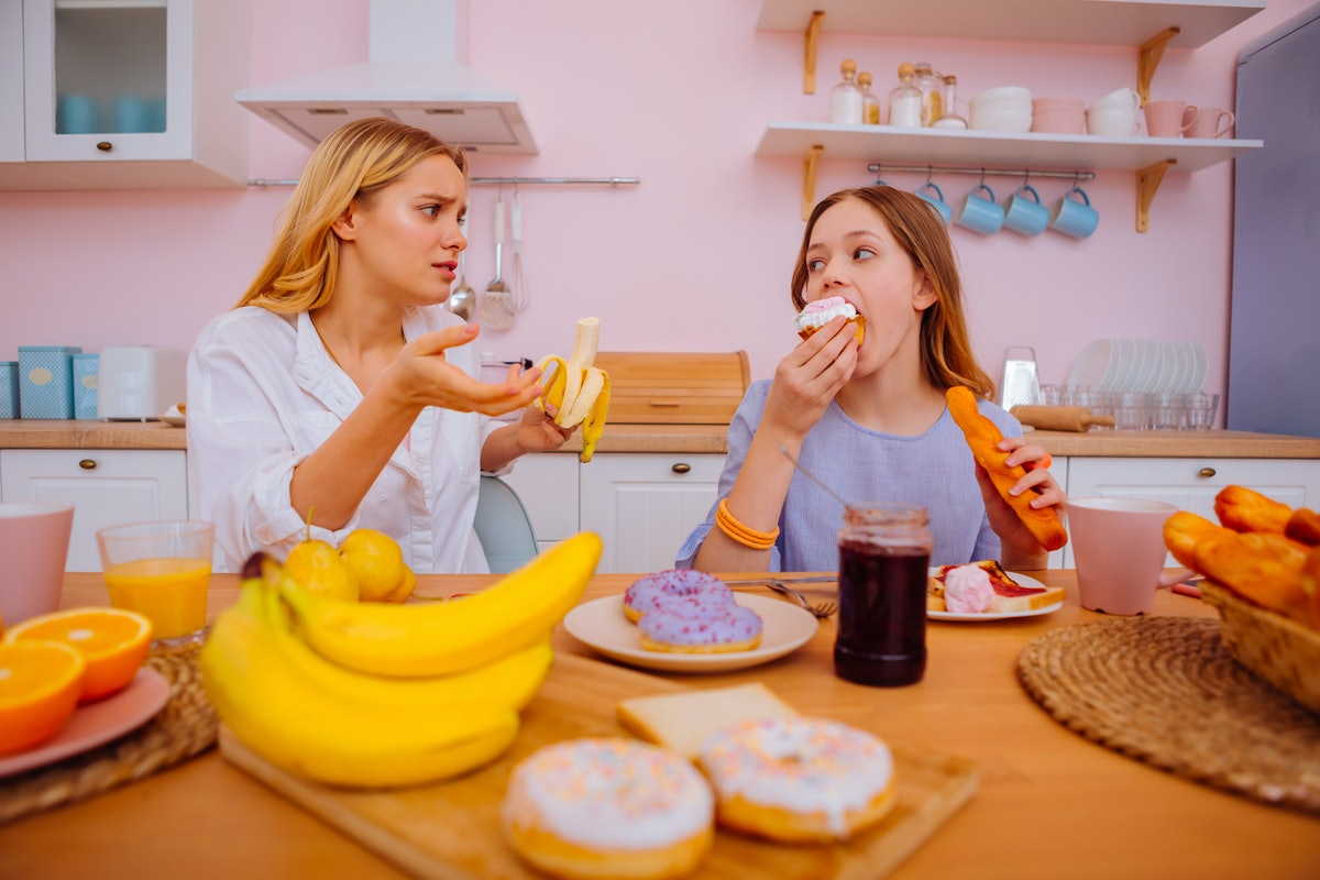 Too many doughnuts. Caring older sister feeling anxious while telling her sibling not to eat many doughnuts