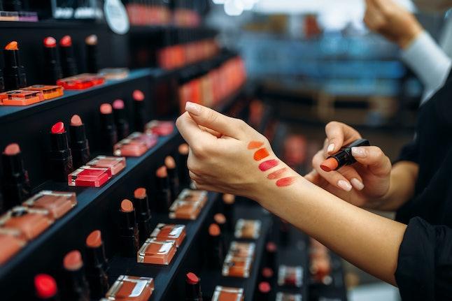 Female customer testing lipstick in make-up shop
