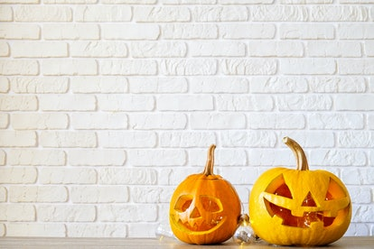 Few orange pumpkins of different size carved into Jack o Lantern on wooden table. Background, copy space, close up, top view. All hallows eve Halloween party decoration. Trick or treat concept.