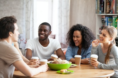Excited young mixed race people listening to best friends joke, laughing, having fun together. Happy millennial best friends gathered in cafe, drinking coffee, spending free time together.