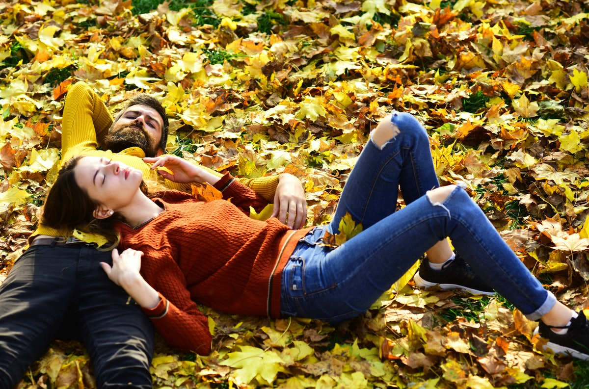 Couple in love lies on dry fallen leaves in park. Man and woman with calm faces on grass and leaves ...