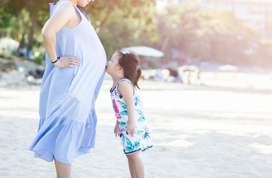 photo of Happy family. Pregnant mother and daughter kissing relaxing and playing on the beach,Happy ...