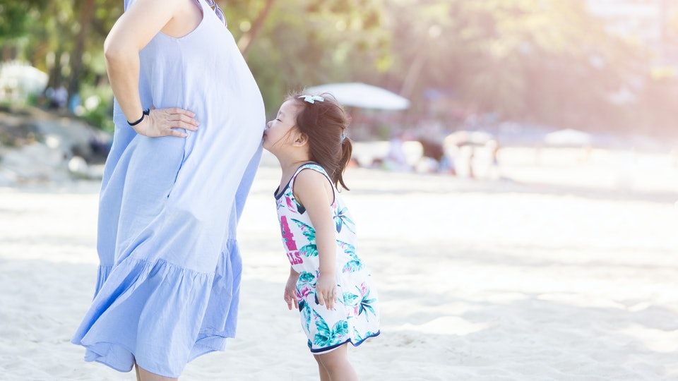 photo of Happy family. Pregnant mother and daughter kissing relaxing and playing on the beach,Happy pregnant woman, little child daughter kissing tummy mother in summer day.