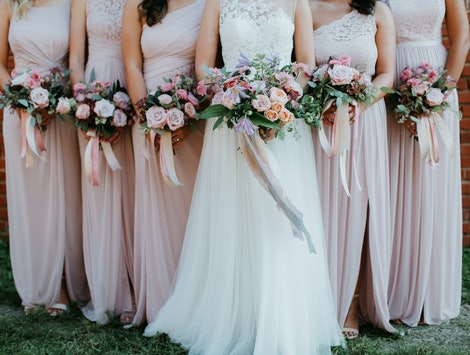 bride and bridesmaids holding wedding bouquets, pink bridesmaids dresses, detail shot, copy space
