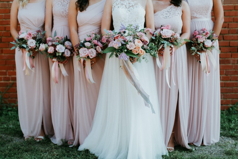 bride and bridesmaids holding wedding bouquets, pink bridesmaids dresses, detail shot, copy space