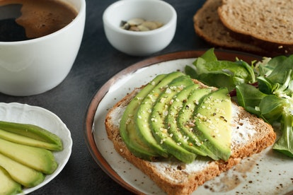 Avocado sandwich on dark rye toast bread made with fresh sliced avocado,  cream cheese and seeds, from above