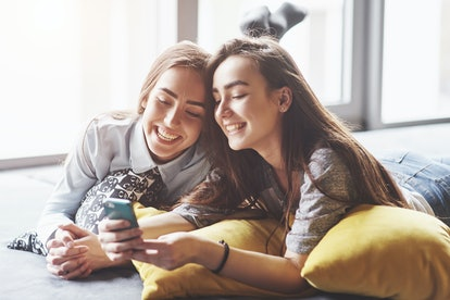 Two cute smiling twins sisters holding smartphone and making selfie. Girls lie on the couch posing and joy.