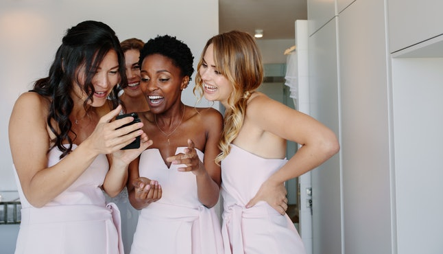 Smiling bridesmaids looking at the photographs of bride on mobile phone in a hotel room on wedding day. Beautiful bride and bridesmaid on the wedding day