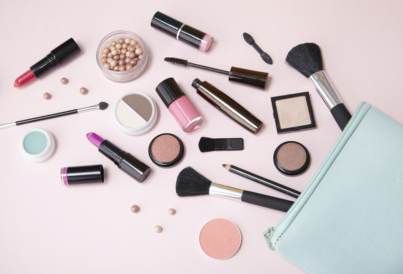 A blue make up bag with cosmetic beauty products spilling out on to a pastel pink background