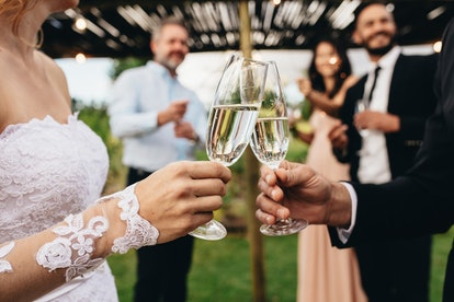 Close up of bride and groom toasting champagne glasses at wedding party. Newlyweds clinking glasses at wedding reception outside.