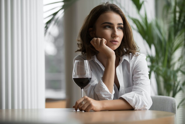 Woman alone with red wine glass sitting in the restaurant and thinking leaning head to hand