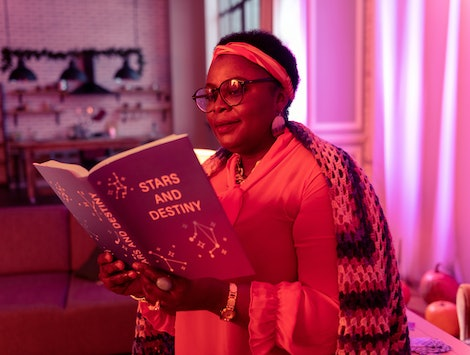 Book on astrology. African american plump fortune-teller wearing eyewear feeling focused while reading a book on astrology