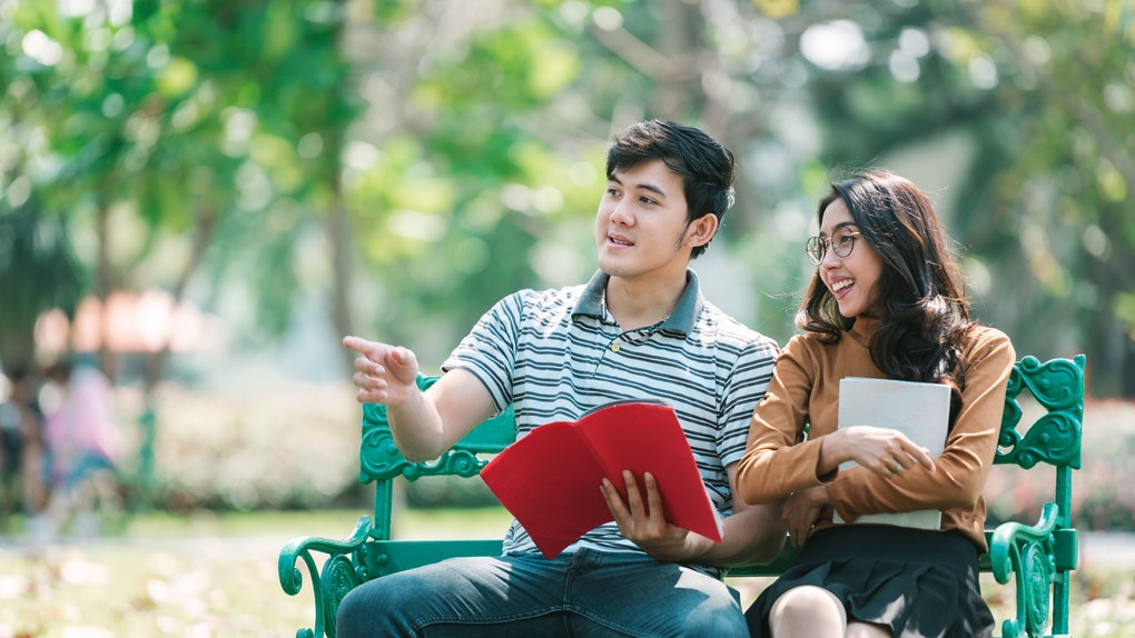 Girl friend and boy friend leaning knowledge by book while there are sitting in the park