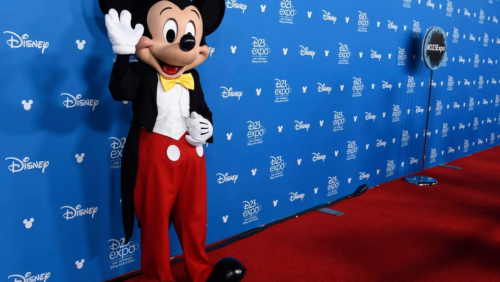 Mickey Mouse waves to members of the media at the Disney Legends press line during the 2019 D23 Expo, in Anaheim, Calif