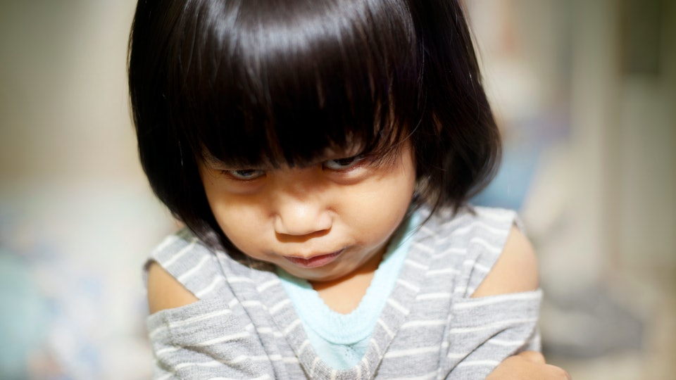 Portrait image of little Asian baby girl gets really angry, looking up to camera