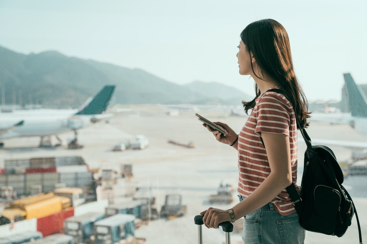 side view of young asian travel woman standing with mobile phone near airport window waiting for fli...