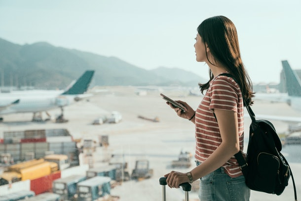 side view of young asian travel woman standing with mobile phone near airport window waiting for flight. beautiful girl with backpack and luggages in hall of lounge area looking out runway airplane