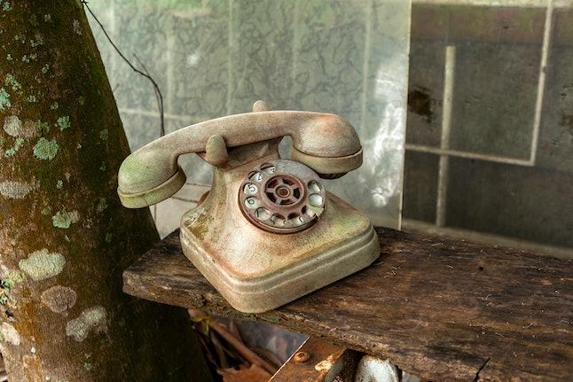 Old dirt broken abandoned disk telephone - no communication offline rusty