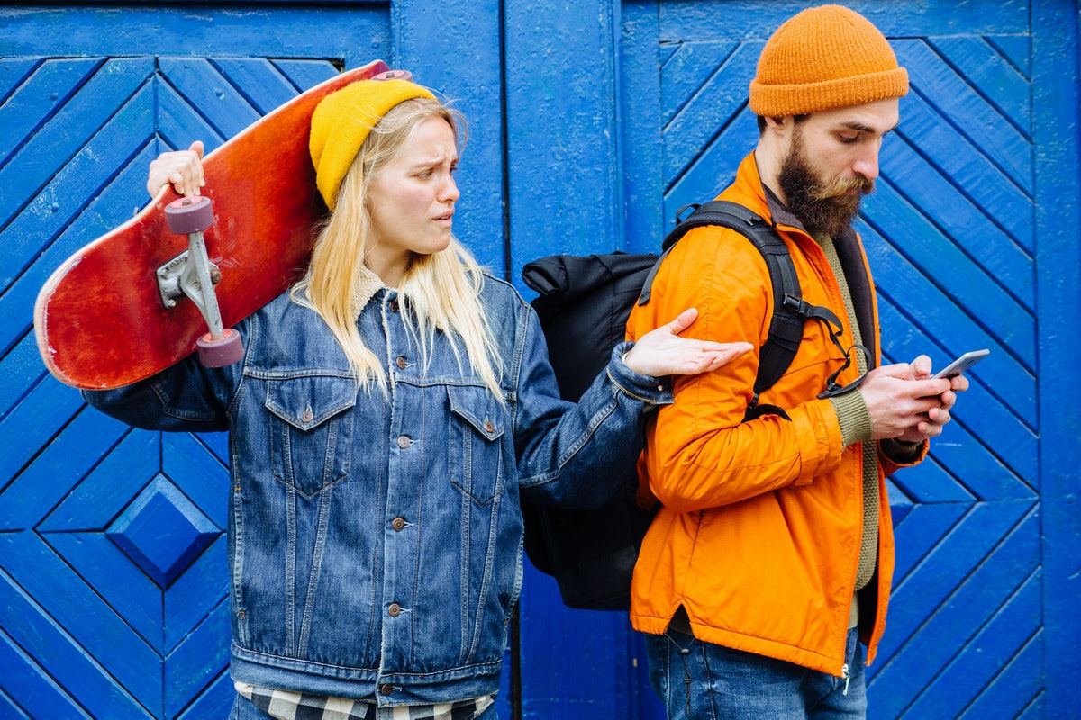 Hipster couple longboarders quarreling - angry furious blond woman looking at her boyfriend's smartphone with negative emotion. Comic shot of hipster couple with skateboard on blue background