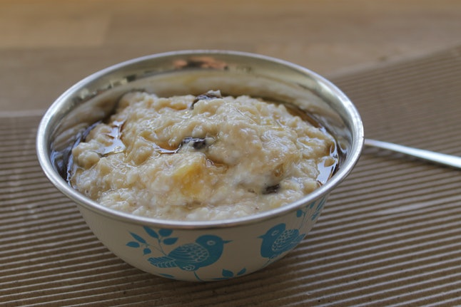 Closeup of banana, raisin and maple syrup oatmeal porridge served in a small white metal bowl decorated with blue birds and placed on a brown surface