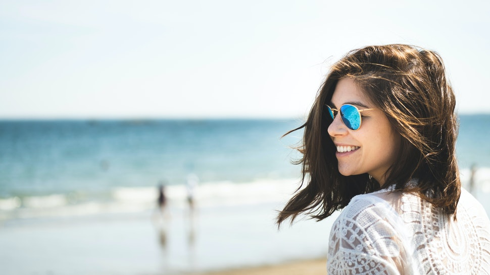 Portrait of beautiful woman having fun on the beach in summer