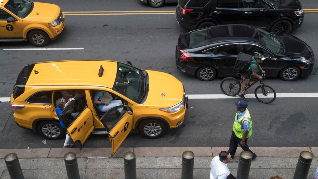 Ride-hailing cars and a a cyclist make their way across 42nd Street as passengers load into a yellow cab outside Grand Central Terminal in New York. Once synonymous with New York City, yellow taxis have been supplanted by an army of black cars that pick up riders though the Uber, Lyft and other apps. The rise in the number of ride-hail vehicles has been so dizzying that the New York City Council is pondering a series of legislative proposals to be voted on Wednesday, Aug. 8