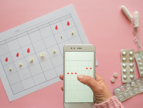 Menstrual cycle. Calendar for the month with marks and a mobile application on the smartphone screen. Tablets and toiletries on a pink background