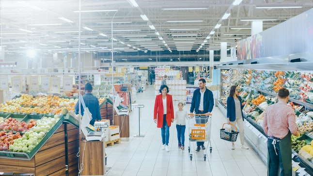 At the Supermarket: Happy Family of Three, Holding Hands, Walks Through Fresh Produce Section of the Store. Father, Mother and Daughter Having Fun Time Shopping. High Angle Panoramic Shot.