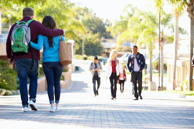 Student Couple Walking Outdoors On University Campus
