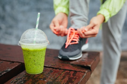 Green detox smoothie cup and woman lacing running shoes before workout on rainy day. Fitness and healthy lifestyle concept.