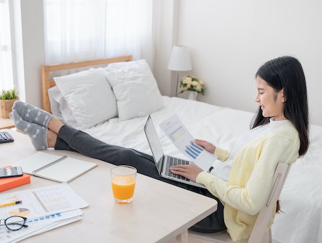 Asian female freelancer reading report paper and working with laptop lay on knee with rest leg on table in bedroom at home.Work at home concept.work from home.relax lifestyle