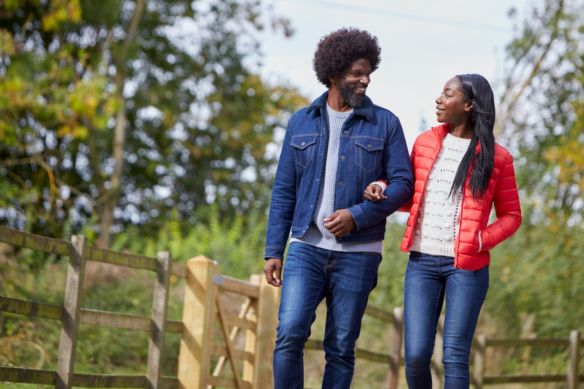 Black adult couple talking and walking  arm in arm in the countryside