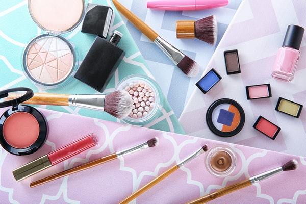 Cosmetic products and brushes on colorful background