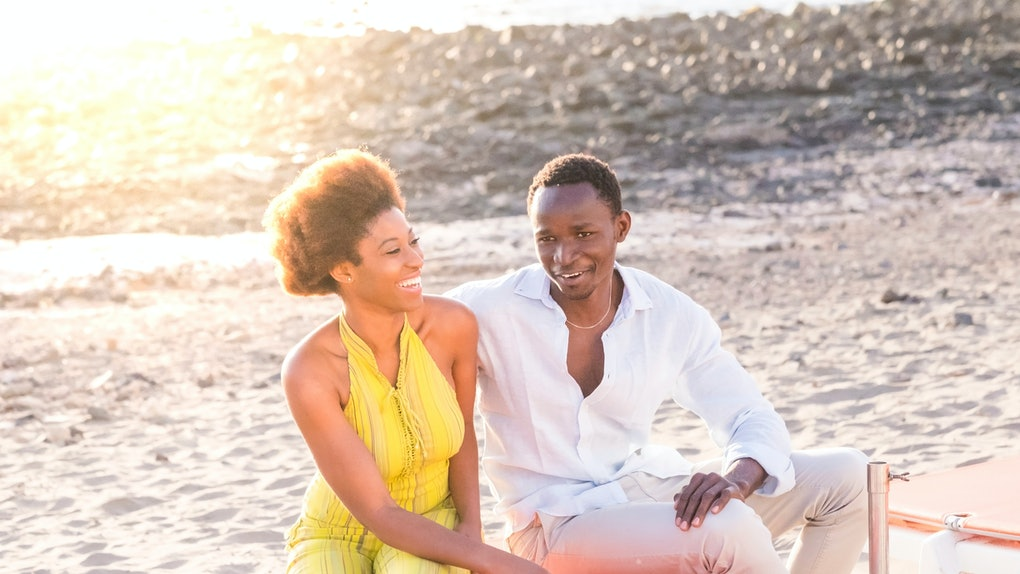Nice young ethnic black african couple sit down outdoor and enjoy the friendship together smiling and having fun - first date and diversity youth people - sun backlight in background
