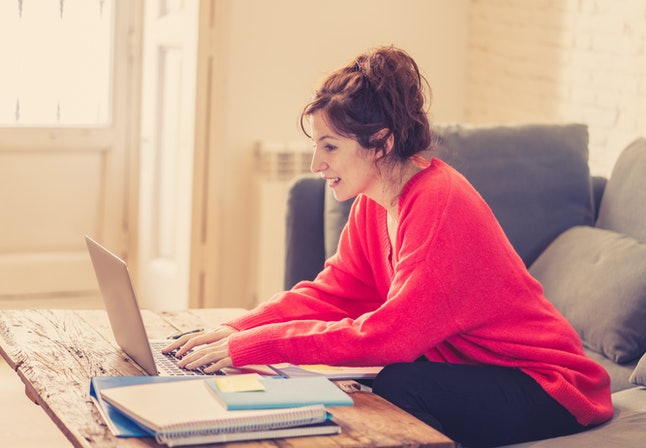 Close up of a thoughtful casual beautiful woman wearing a bright red pullover working and studying on a laptop sitting on the couch at home. In working from home and surfing on the Internet concept.