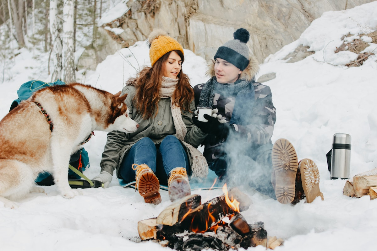 The happy couple with dog haski at the forest nature park in the cold season. Travel adventure love ...