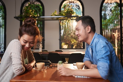 Side view portrait of loving Asian couple meeting in cafe for date, chatting and flirting affectiona...