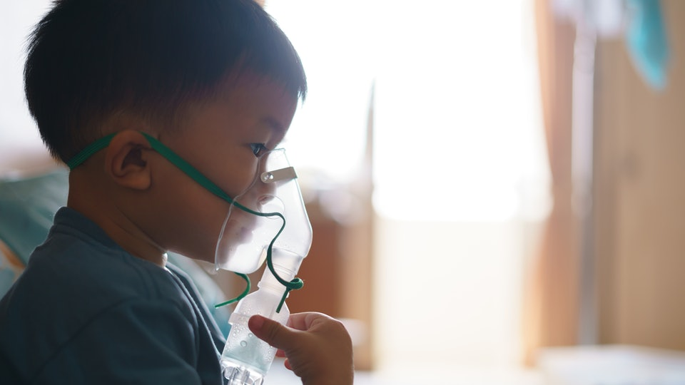 Sick Asian boy about 2 years and 8 months in hospital using inhaler containing medicine to stop coughing from disease like flu or RSV, Respiratory Syncytial Virus