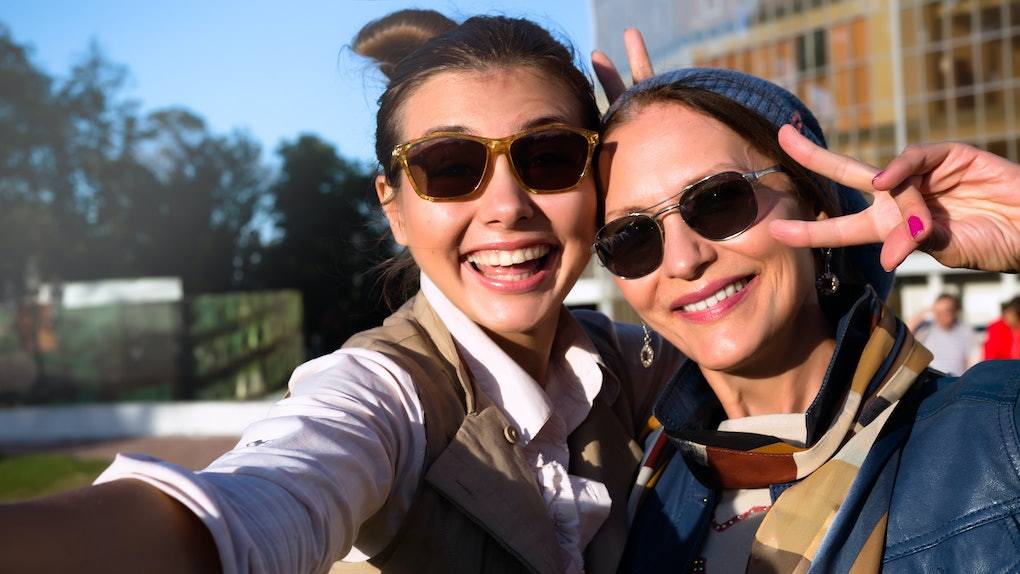 A mom and adult daughter smile and pose for a selfie on a sunny day in a park.