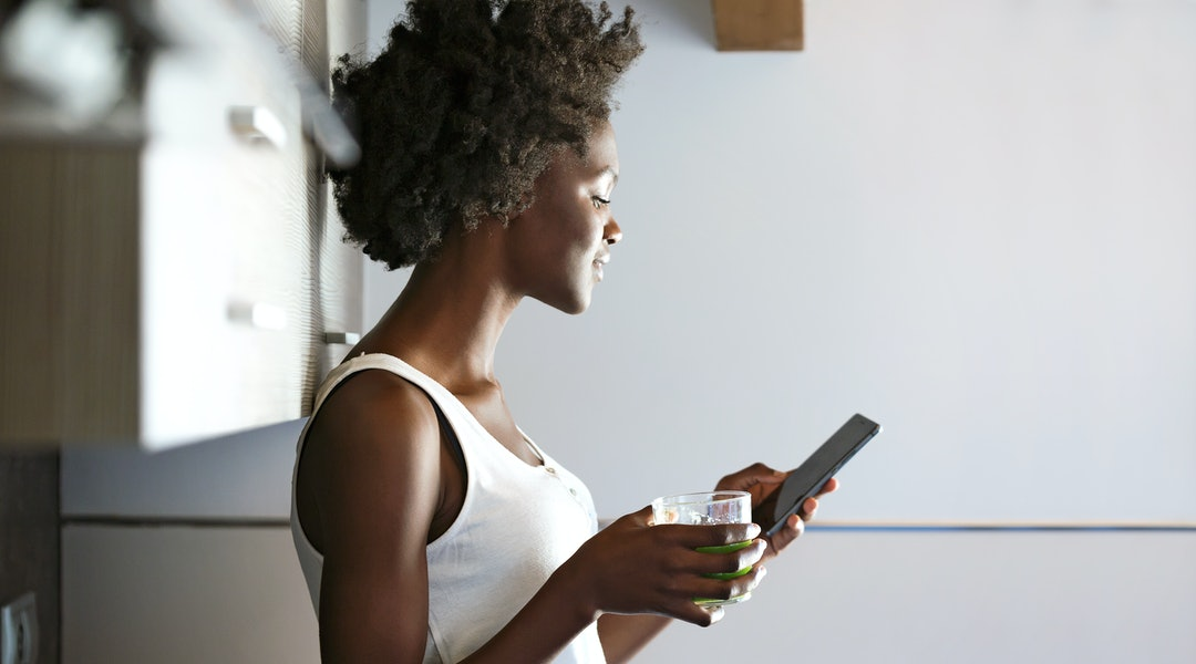 Shot of beautiful young woman drinking green detox juice and using her mobile phone at home.
