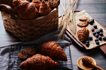 Basket with bread and croissants on the table, croissants and chocolate chip cookies, honey and a board with a small croissant and blueberries
