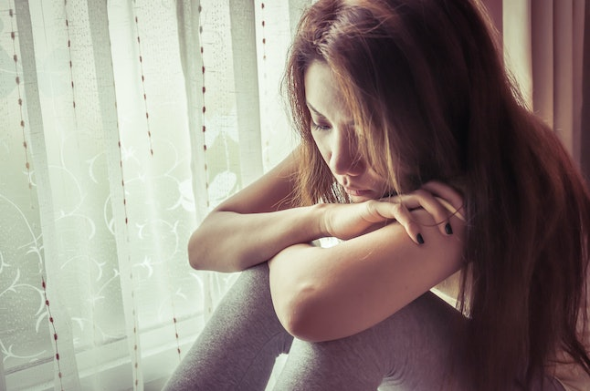 young sad woman sit beside window with vintage filter effect
