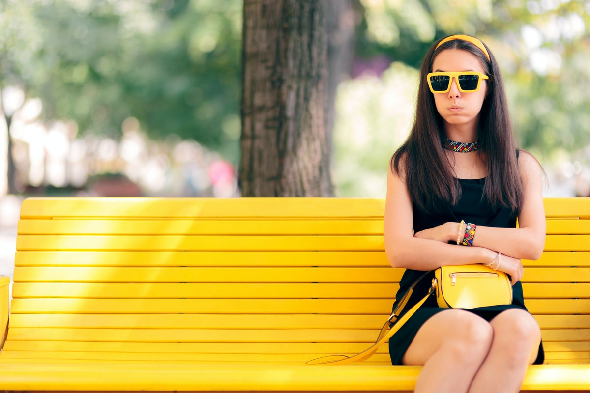 Bored Woman Waiting for her Date Alone on a Bench. Funny girlfriend waiting for her boyfriend out in the city
