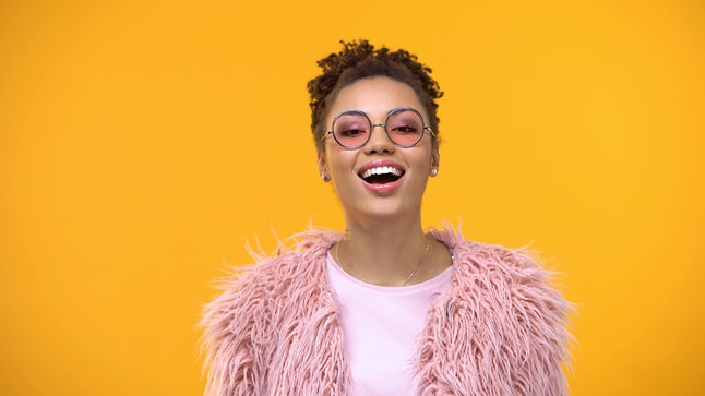 Joyful young female in fashionable eyeglasses and fur on yellow background