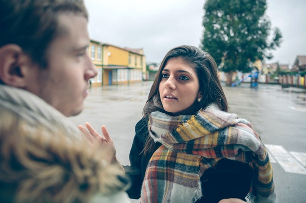 Portrait of angry woman having argument to young man during a hard quarrel outdoors. Couple relationships and problems concept.