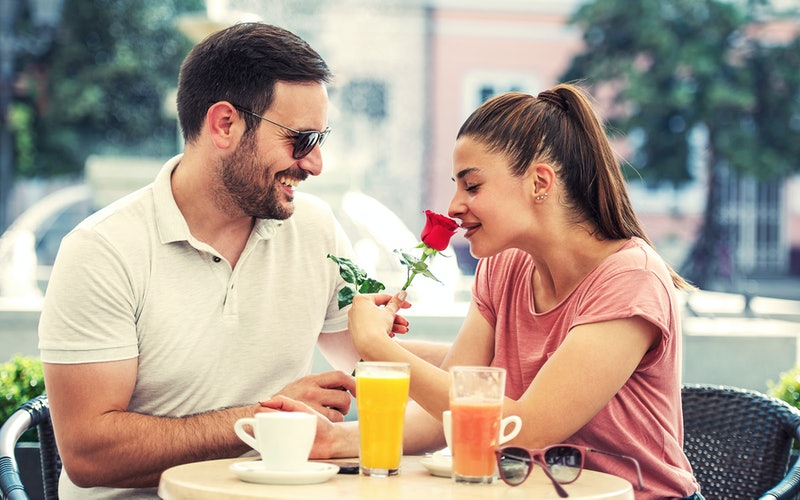 Red rose for a girlfriend. Romantic couple sitting in a cafe drinking coffee and enjoying in conversation. Love, romance, dating