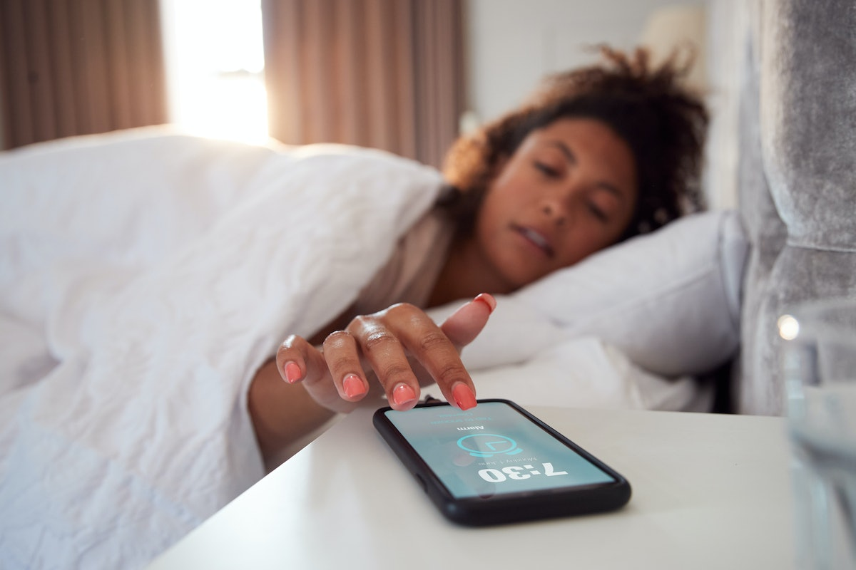 Woman Waking Up In Bed Reaches Out To Turn Off Alarm On Mobile Phone