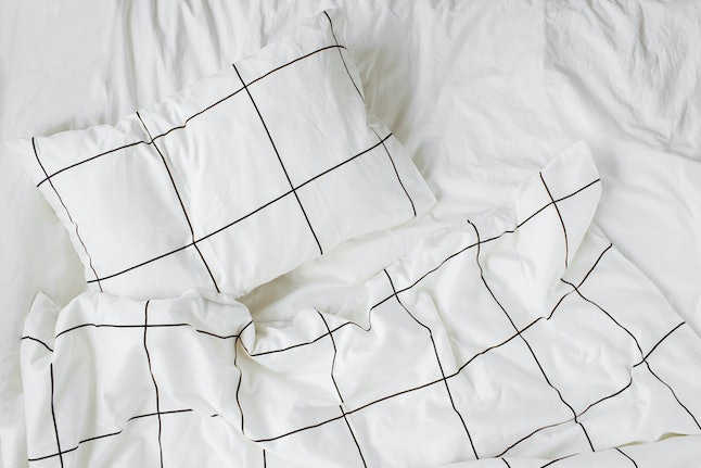 White bedding sheets with striped blanket and pillow. Messy bed. Cozy background.