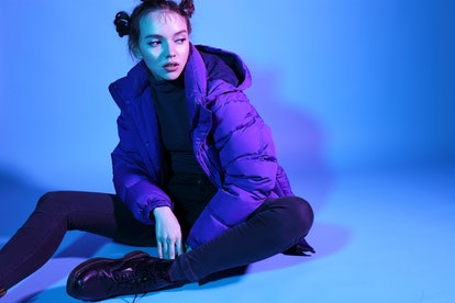Young fashion woman in short violet down jacket and leather boots, asian fashion