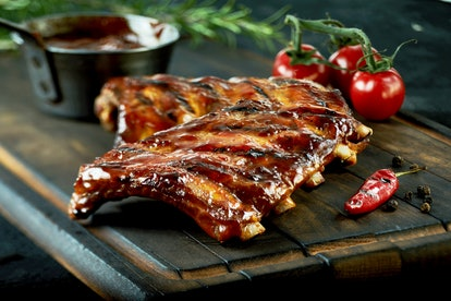Spicy hot grilled spare ribs from a summer BBQ served with a hot chili pepper and fresh tomatoes on an old vintage wooden cutting board